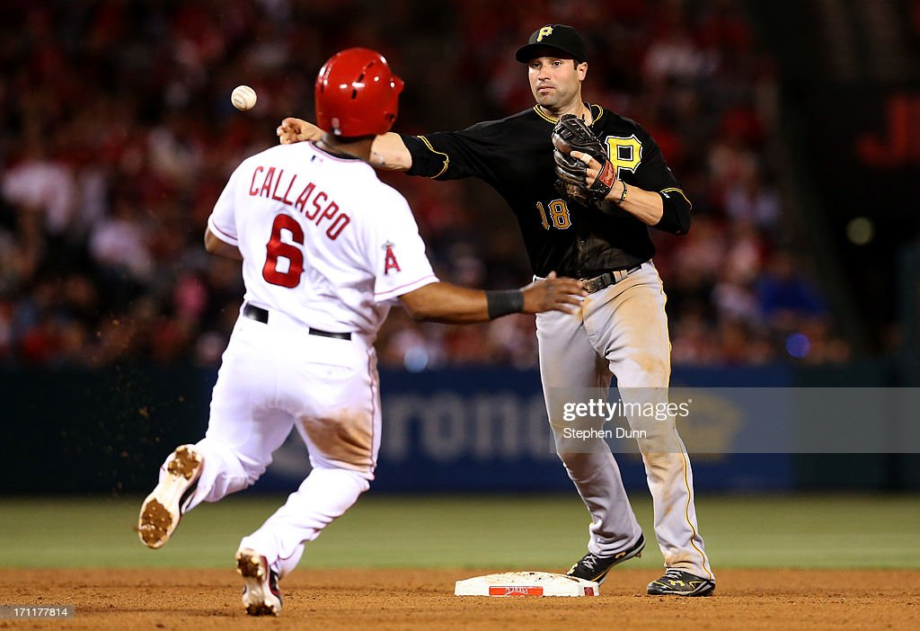 Second baseman Neil Walker #18 of the Pittsburgh Pirates throws to first to complete a double play ending the eighth inning after forcing out Alberto Callaspo #6 of the Los Angeles Angels of Anaheim at Angel Stadium of Anaheim on June 22, 2013 in Anaheim, California.