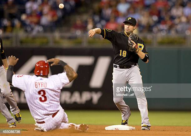Second baseman Neil Walker of the Pittsburgh Pirates turns a double play over Marlon Byrd of the Philadelphia Phillies in the bottom of the fourth...