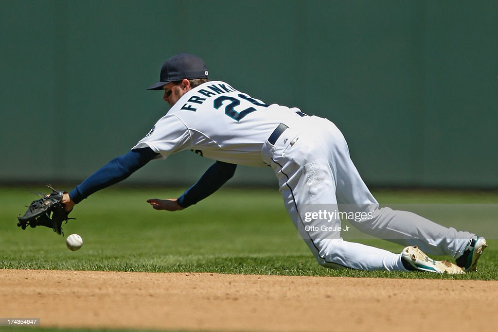 Second baseman Nick Franklin #20 of the Seattle Mariners dives for a single by Yan Gomes of the Cleveland Indians in the fourth inning at Safeco Field on July 24, 2013 in Seattle, Washington.