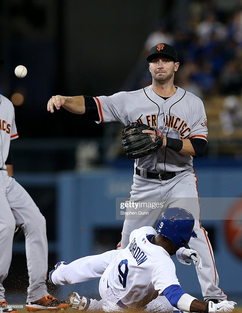 Second baseman Nick Noonan #21 of the San Francisco Giants throws to first to turn a double play after forcing out <a gi-track='captionPersonalityLinkClicked' href=/galleries/search?phrase=Dee+Gordon&family=editorial&specificpeople=7091343 ng-click='$event.stopPropagation()'>Dee Gordon</a> #9 of the Los Angeles Dodgers in the eighth inning at Dodger Stadium on September 14, 2013 in Los Angeles, California.