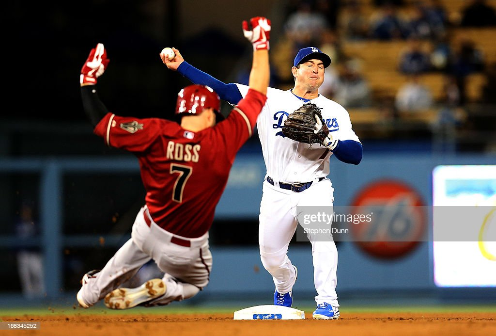 Second baseman Nick Punto #7 of the Los Angeles Dodgers throws to first to complete a double play after forcing out Cody Ross #7 of the Arizona Diamondbacks in the sixth inning at Dodger Stadium on May 8, 2013 in Los Angeles, California.