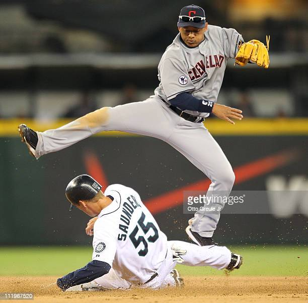 Second baseman Orlando Cabrera of the Cleveland Indians hops over Michael Saunders of the Seattle Mariners on a double play in the fifth inning at...