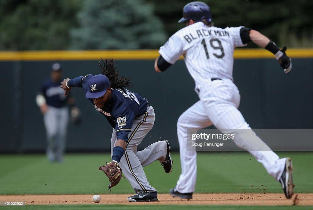 Second baseman Rickie Weeks #23 of the Milwaukee Brewers commits an error on a ground ball by Drew Stubbs #13 of the Colorado Rockies allowing Charlie Blackmon #19 of the Colorado Rockies to advance to second base in the first inning at Coors Field on June 21, 2014 in Denver, Colorado.