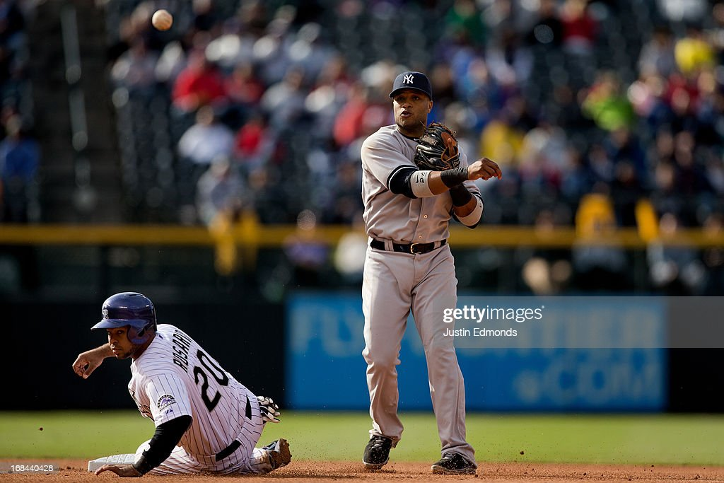 Second baseman <a gi-track='captionPersonalityLinkClicked' href=/galleries/search?phrase=Robinson+Cano&family=editorial&specificpeople=538362 ng-click='$event.stopPropagation()'>Robinson Cano</a> #24 of the New York Yankees throws to first base to complete the double play as <a gi-track='captionPersonalityLinkClicked' href=/galleries/search?phrase=Wilin+Rosario&family=editorial&specificpeople=5734314 ng-click='$event.stopPropagation()'>Wilin Rosario</a> #20 of the Colorado Rockies slides at second during the seventh inning at Coors Field on May 9, 2013 in Denver, Colorado. The Yankees defeated the Rockies 3-1 to win the series.