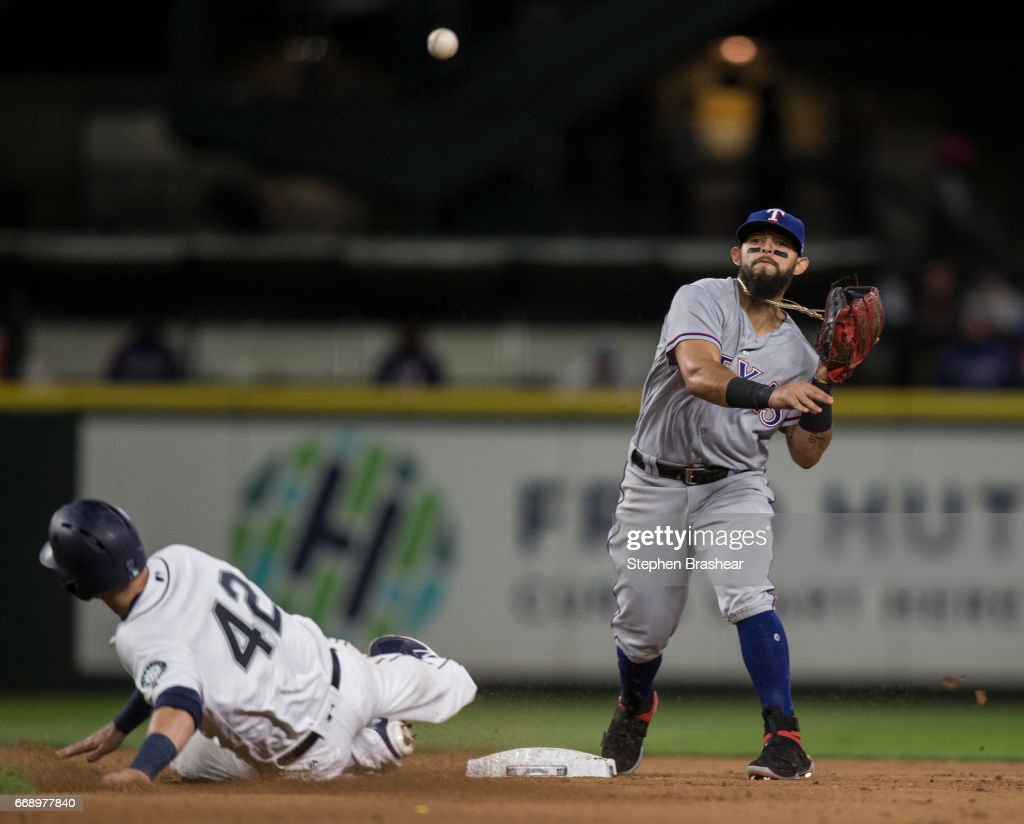 Second baseman Rougned Odor #12 forces out Mitch Haniger #17 of the Seattle Mariners at second base as he turns the double play on a ball hit by Robinson Cano #22 of the Seattle Mariners during the seventh inning of a game at Safeco Field on April 15, 2017 in Seattle, Washington. The Mariners won the game 5-0. All players are wearing #42 in honor of Jackie Robinson Day.