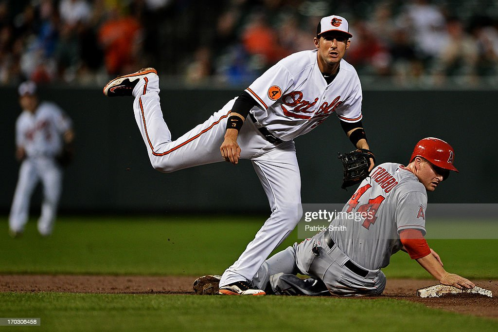 Second baseman <a gi-track='captionPersonalityLinkClicked' href=/galleries/search?phrase=Ryan+Flaherty&family=editorial&specificpeople=4412528 ng-click='$event.stopPropagation()'>Ryan Flaherty</a> #3 of the Baltimore Orioles makes a double play as <a gi-track='captionPersonalityLinkClicked' href=/galleries/search?phrase=Mark+Trumbo&family=editorial&specificpeople=4921667 ng-click='$event.stopPropagation()'>Mark Trumbo</a> #44 of the Los Angeles Angels of Anaheim slides into second base in the fourth inning at Oriole Park at Camden Yards on June 10, 2013 in Baltimore, Maryland.