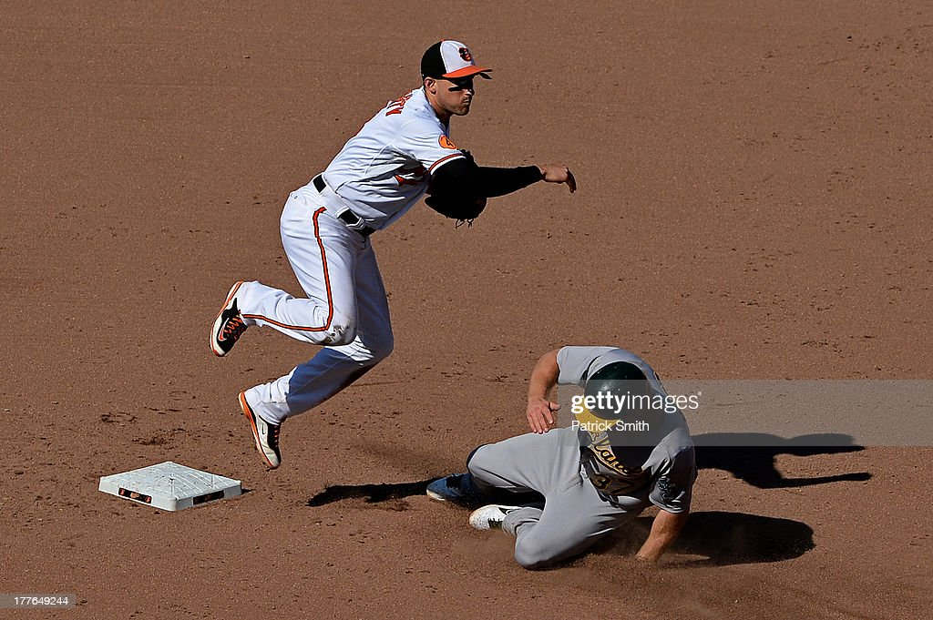 Second baseman <a gi-track='captionPersonalityLinkClicked' href=/galleries/search?phrase=Ryan+Flaherty&family=editorial&specificpeople=4412528 ng-click='$event.stopPropagation()'>Ryan Flaherty</a> #3 of the Baltimore Orioles turns the double play as <a gi-track='captionPersonalityLinkClicked' href=/galleries/search?phrase=Brandon+Moss&family=editorial&specificpeople=702783 ng-click='$event.stopPropagation()'>Brandon Moss</a> #47 of the Oakland Athletics slides into second base in the eighth inning at Oriole Park at Camden Yards on August 25, 2013 in Baltimore, Maryland. The Baltimore Orioles won, 10-3.