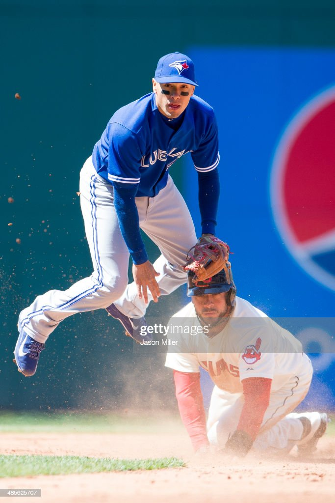 Second baseman <a gi-track='captionPersonalityLinkClicked' href=/galleries/search?phrase=Ryan+Goins&family=editorial&specificpeople=9004043 ng-click='$event.stopPropagation()'>Ryan Goins</a> #17 of the Toronto Blue Jays jumps over <a gi-track='captionPersonalityLinkClicked' href=/galleries/search?phrase=Mike+Aviles&family=editorial&specificpeople=4944765 ng-click='$event.stopPropagation()'>Mike Aviles</a> #4 of the Cleveland Indians after throwing to first for a double play off a ground ball hit by Asdrubal Cabrera #13 of the Cleveland Indians to end the fifth inning at Progressive Field on April 19, 2014 in Cleveland, Ohio.