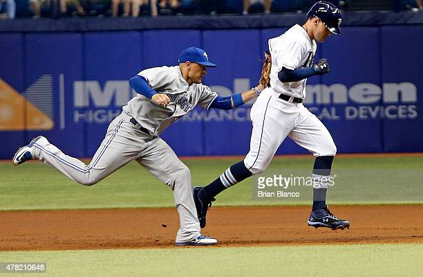 Second baseman Ryan Goins of the Toronto Blue Jays runs down Brandon Guyer of the Tampa Bay Rays for the out as Guyer runs back to first base after...