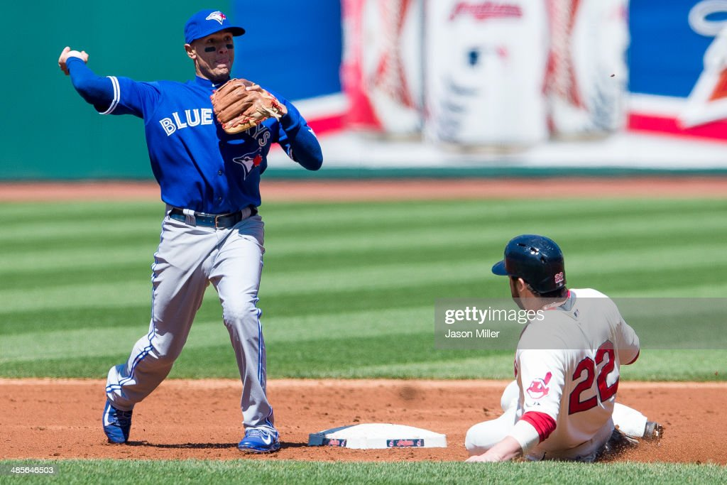 Second baseman <a gi-track='captionPersonalityLinkClicked' href=/galleries/search?phrase=Ryan+Goins&family=editorial&specificpeople=9004043 ng-click='$event.stopPropagation()'>Ryan Goins</a> #17 of the Toronto Blue Jays throws out Carlos Santana #41 at first as <a gi-track='captionPersonalityLinkClicked' href=/galleries/search?phrase=Jason+Kipnis&family=editorial&specificpeople=5330784 ng-click='$event.stopPropagation()'>Jason Kipnis</a> #22 of the Cleveland Indians is out at second during the first inning at Progressive Field on April 19, 2014 in Cleveland, Ohio.