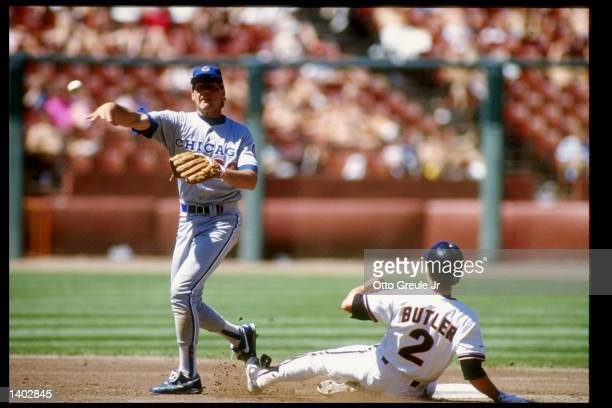 Second baseman Ryne Sandberg of the Chicago Cubs throws to first after stepping on second and forcing Brett Butler of the San Francisco Giants out...