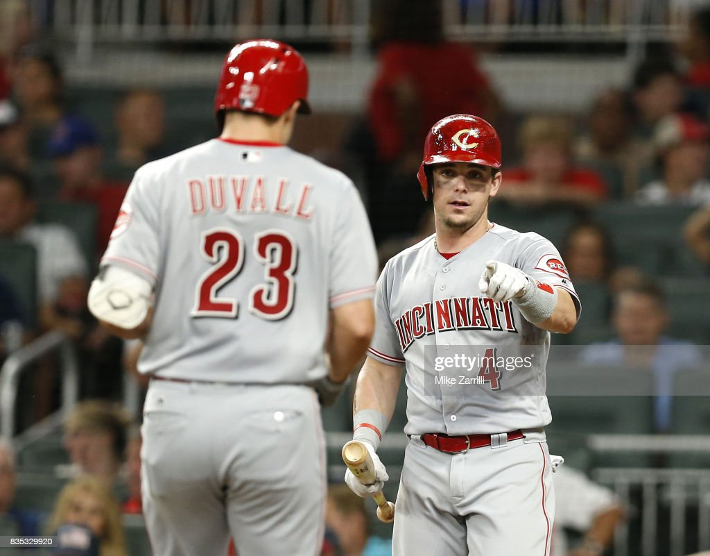 Second baseman Scooter Gennett #4 of the Cincinnati Reds acknowledges left fielder Adam Duvall #23 after Duvall's home run in the sixth inning during the game against the Atlanta Braves at SunTrust Park on August 18, 2017 in Atlanta, Georgia.