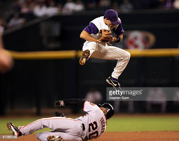 Second baseman Scott Hairston of the Arizona Diamondbacks leaps over a sliding Michael Tucker of the San Francisco Giants after Hairston forced out...