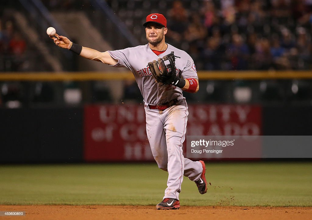 Second baseman Skip Schumaker of the Cincinnati Reds throws out a runner against the Colorado Rockies at Coors Field on August 14 2014 in Denver...