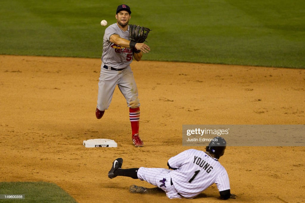 Second baseman Skip Schumaker of the St Louis Cardinals throws to first base to complete the double play as Eric Young Jr #1 of the Colorado Rockies...