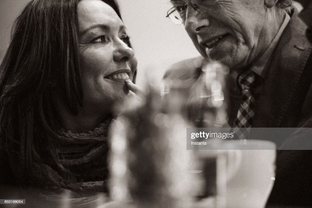 A second chance... Romantic evening in a cafe for a mature couple falling in love after some years of solitude. : Stock Photo