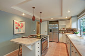 Second floor Kitchen boasts tray ceiling, island and white shaker cabinets. Fresh natural colors create cozy atmosphere.
