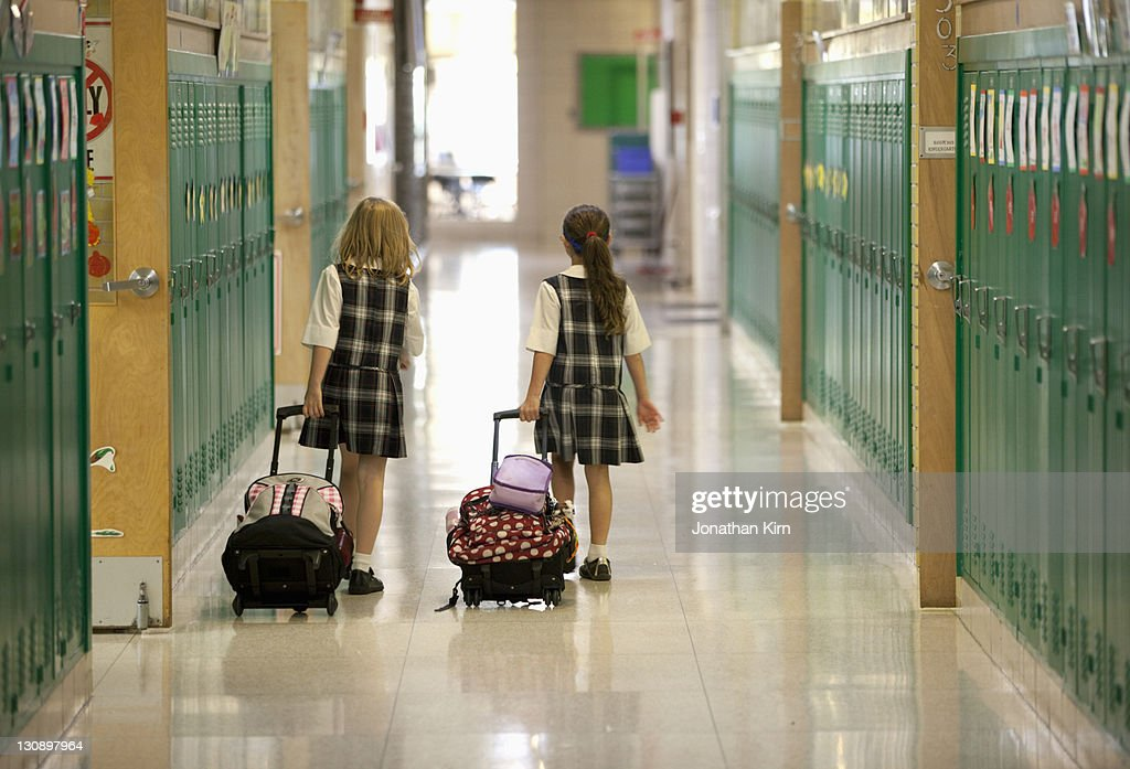 Second grade girls roll backpacks in school. : Stock Photo
