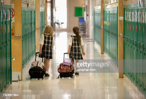 Second Grade Girls Roll Backpacks In School Stock Photo | Getty Images
