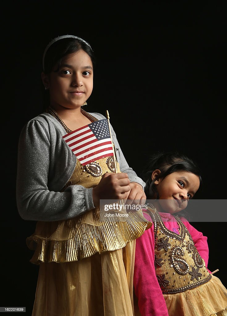 Second grade student Maria Rahman, 7, born in Bangladesh, holds a flag given to her by the U.S. Citizenship and Immigration Services (USCIS), while waiting to receive her citizenship certificate on February 19, 2013 in New York City. Her younger sister Mayisah Rahman, 3, (R), was born in the United States. Her father, Mizanur Rahman, a taxi driver, is a naturalized American from Bangladesh, and their family lives in the Bronx, New York City. Almost 300 foreign-born children of naturalized Americans received citizenship certificates Tuesday at the USCIS center during the special event. Children of naturalized immigrants receive U.S. citizenship if they arrive to the United States as minors, but they must go through a process at USCIS to receive official citizenship documents proving they have become Americans.