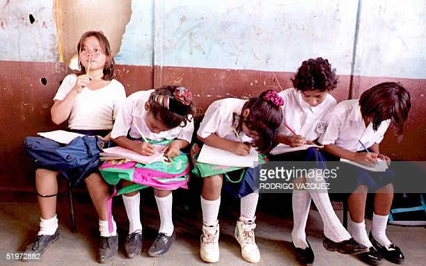 Second grade students at the Jonathan Gonzalez school in ManaguaNicaraguashare a bench while using their laps to take notes 24 April due to the lack...