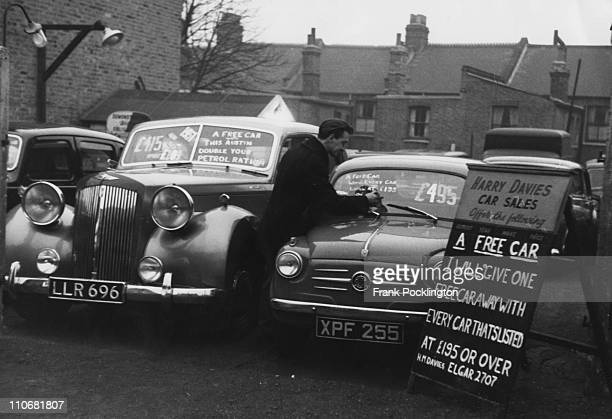 Second hand car dealer Harry Davies on his lot in Harlesden London 1957 In response to petrol rationing Davies is offering a free car with every car...