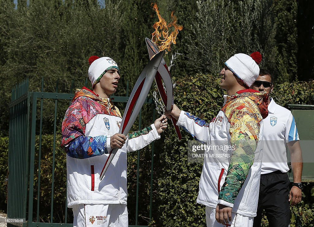 Second Olympic Flame torchbearer Russian ice hockey player Alexander Ovechkin (R) receives the flame from the first torchbearer Greek skier Giannis Antoniou (R) near the monument of Pierre de Coubertin, French founder of the International Olympic Committee, during the torch relay after the Olympic Flame Lighting Ceremony at the ancient stadium of Olympia, on September 29, 2013. The flame will be transported by torch relay to the Russian resort of Sochi, which will host the 2014 Winter Olympic Games from February 7 to 23.