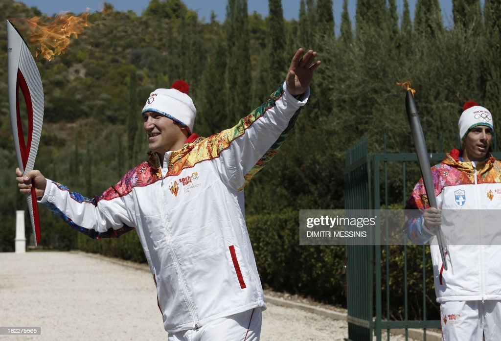 Second Olympic Flame torchbearer Russian ice hockey player Alexander Ovechkin (L) gestures as he departs from the monument of Pierre de Coubertin, French founder of the International Olympic Committee, after receiving the flame from the first torchbearer Greek skier Giannis Antoniou (R) during the torch relay after the Olympic Flame Lighting Ceremony at the ancient stadium of Olympia, on September 29, 2013. The flame will be transported by torch relay to the Russian resort of Sochi, which will host the 2014 Winter Olympic Games from February 7 to 23.