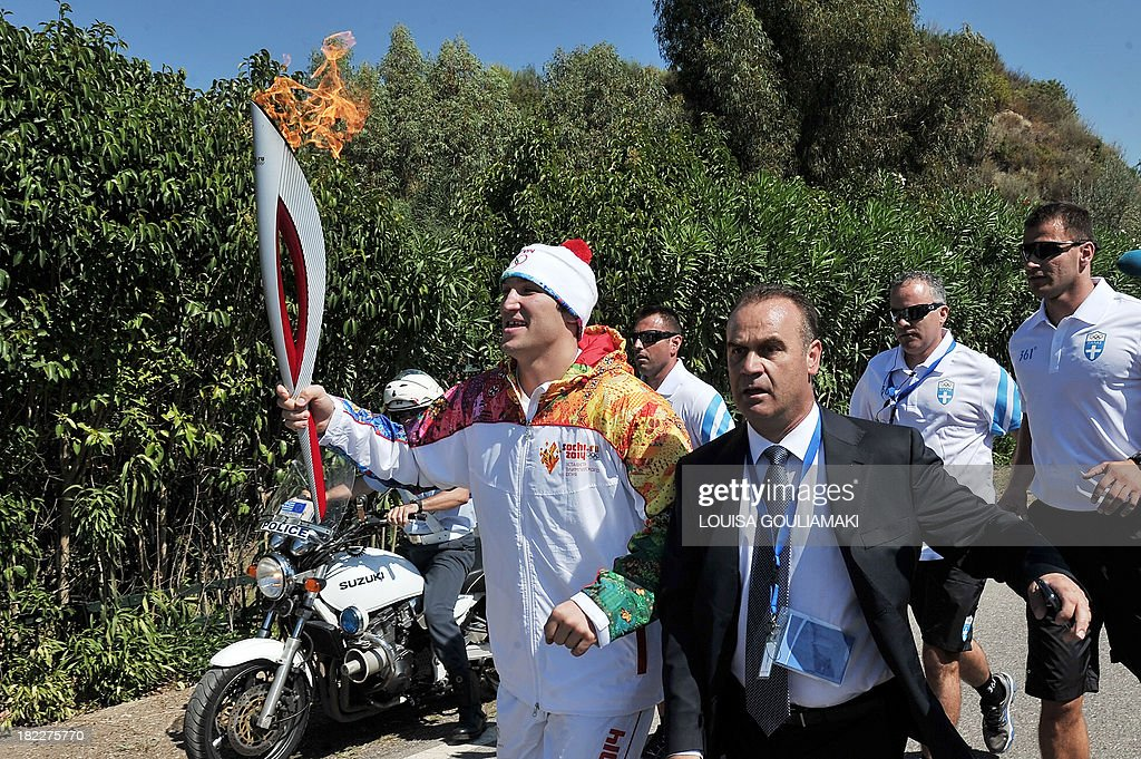 Second Olympic torchbearer Russian ice hockey player Alexander Ovechkin (L) runs with the Olympic Flame after receiving it from the first torchbearer Greek skier Giannis Antoniou (unseen) on September 29, 2013 in ancient Olympia, the sanctuary where the Olympic Games were born in 776 B.C, ahead of the 2014 Sochi Winter Olympic Games. The flame will be transported by torch relay to the Russian resort of Sochi, which will host the 2014 Winter Olympic Games from February 7 to 23. AFP PHOTO / LOUISA GOULIAMAKI