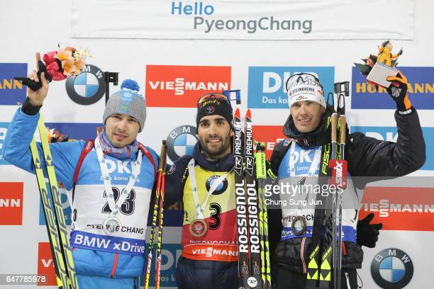 Second place Anton Shipulin of Russia first place Martin Fourcade of France and third place Julian Eberhard of Austria celebrate during the flower...