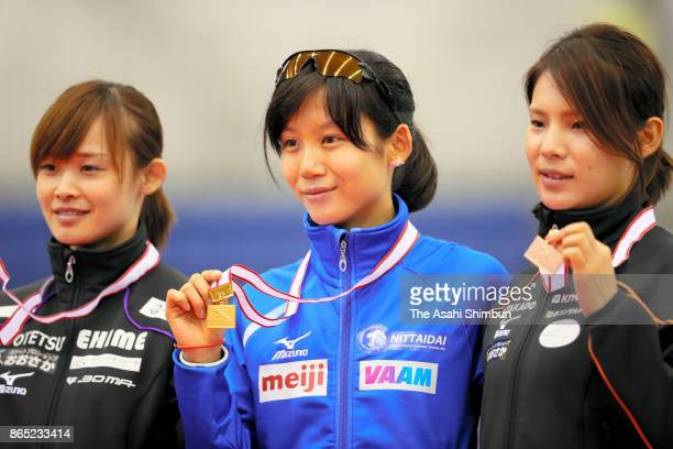 Second place Arisa Go first place Miho Takagi and third place Erina Kamiya pose for photographs on the podium at the medal ceremony for Women's 1000m...