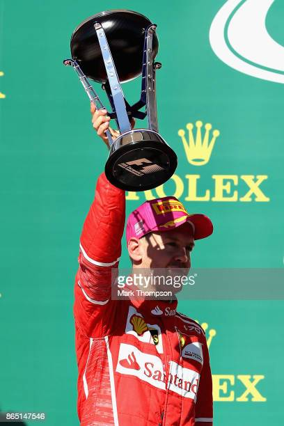 Second place finisher Sebastian Vettel of Germany and Ferrari celebrates on the podium during the United States Formula One Grand Prix at Circuit of...