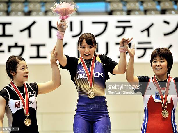 second place Hiromi Miyake winner Kanae Yagi and third place Misaki Gushiken pose for photographs on the podium during the award ceremony for the...