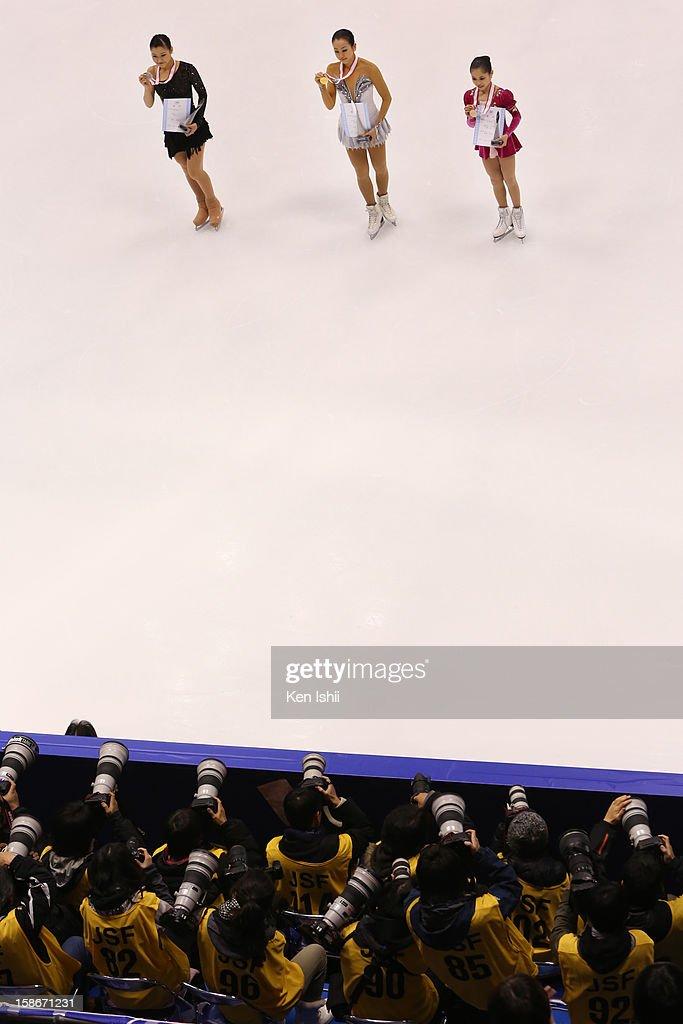 Second place Kanako Murakami, first place Mao Asada, third place Satoko Miyahara pose for photographs during day three of the 81st Japan Figure Skating Championships at Makomanai Sekisui Heim Ice Arena on December 23, 2012 in Sapporo, Japan.