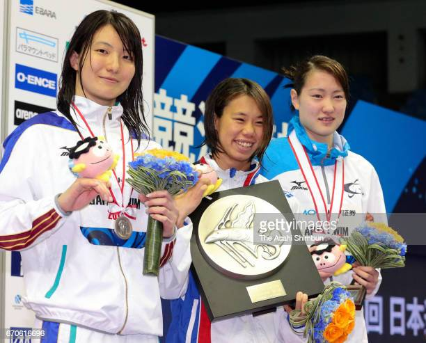 Second place Miyuki Takemura winner Anna Konishi and third place Natsumi Sakai celebrate on the podium at the medal ceremony for the Women's 100m...