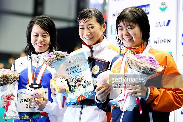 Second place Natsumi Hoshi winner Rikako Ikee and third place Suzuka Hasegawa celebrate on the podium for the Women's 100m Butterfly during day two...