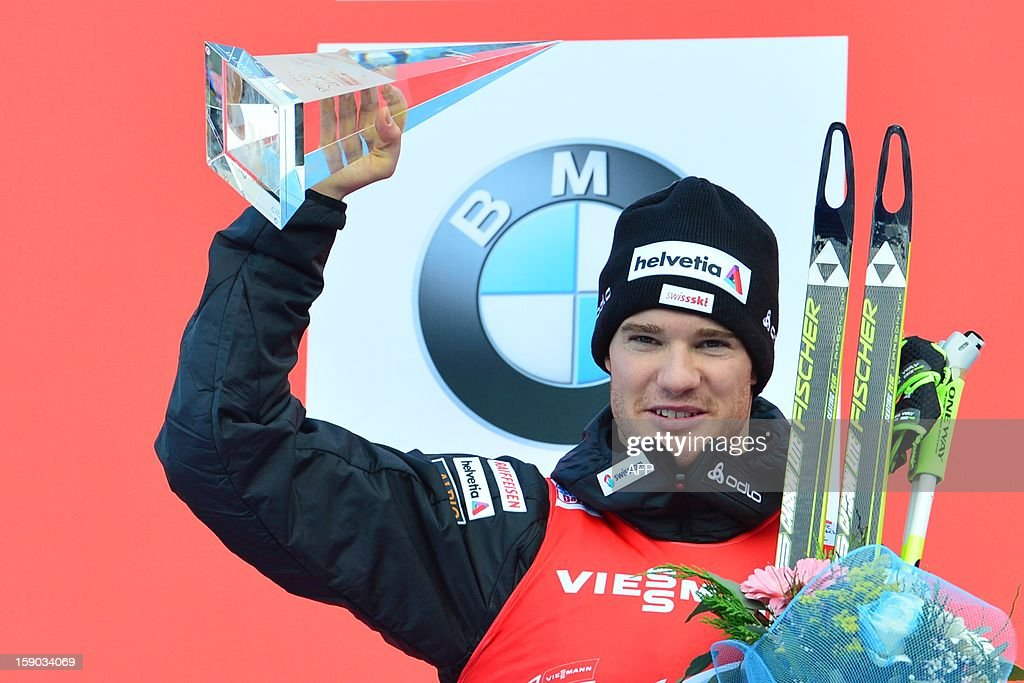 Second place Swiss Dario Cologna of Swiss celebrates on the podium the men's nine km free final climb pursuit race nine of the Tour de Ski in Val di Fiemme on January 6, 2013. AFP PHOTO / GIUSEPPE CACACE AFP PHOTO / GIUSEPPE CACACE