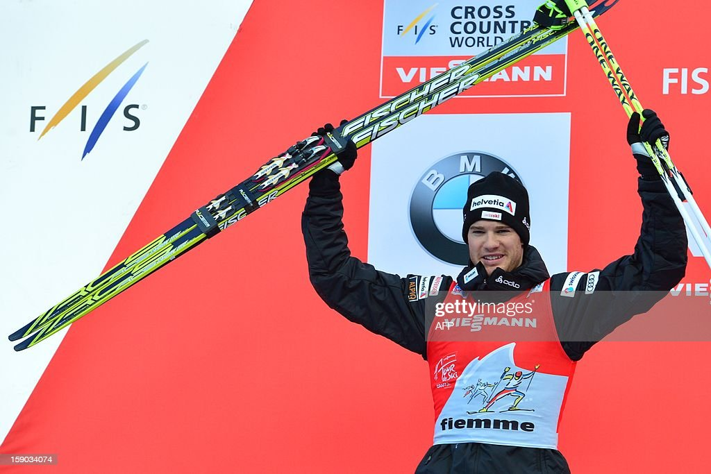 Second place Swiss Dario Cologna of Swiss celebrates on the podium the men's nine km free final climb pursuit race nine of the Tour de Ski in Val di Fiemme on January 6, 2013. AFP PHOTO / GIUSEPPE CACACE AFP PHOTO / GIUSEPPE CACACE
