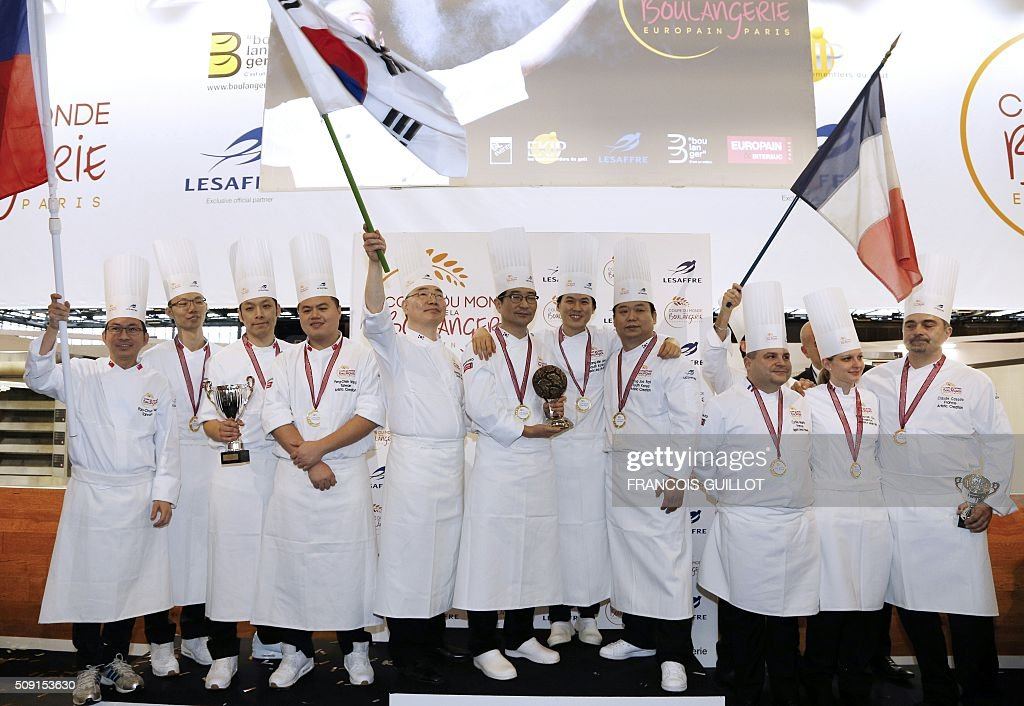 Second place Taiwan's team, first place South Korea's team and third place France's team celebrate on the podium with their trophies and national flags during the Bakery world cup, as part of the Europain fair, on February 9, 2016, in Villepinte near Paris. / AFP / FRANCOIS GUILLOT