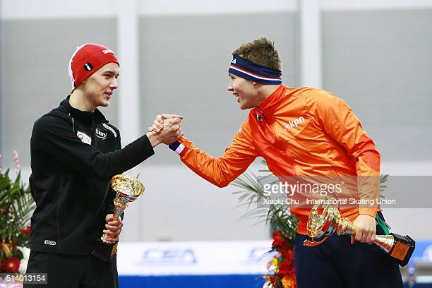 Second place winner Allan Dahl Johansson of Norway and first place winner Marcel Bosker of Netherlands celebrate on the podium after the Men Mass...