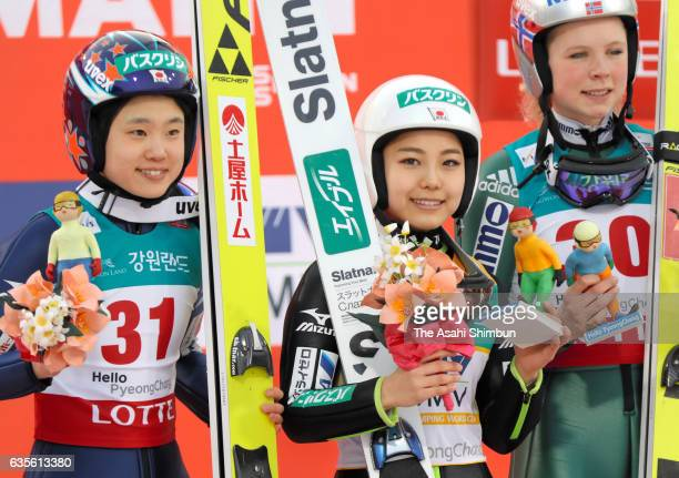Second place Yuki Ito of Japan first place Sara Takanashi of Japan and third place Maren Lundby of Norway celebrate on the podium at the award...