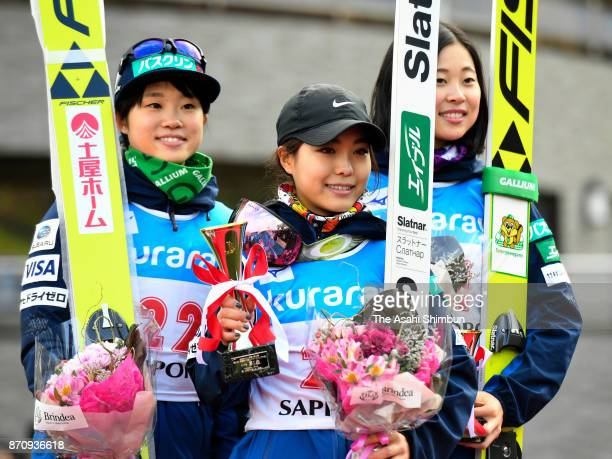 Second place Yuki Ito winner Sara Takanashi and third place Yuka Seto pose on the podium at the medal ceremony for the women's event during the 11th...
