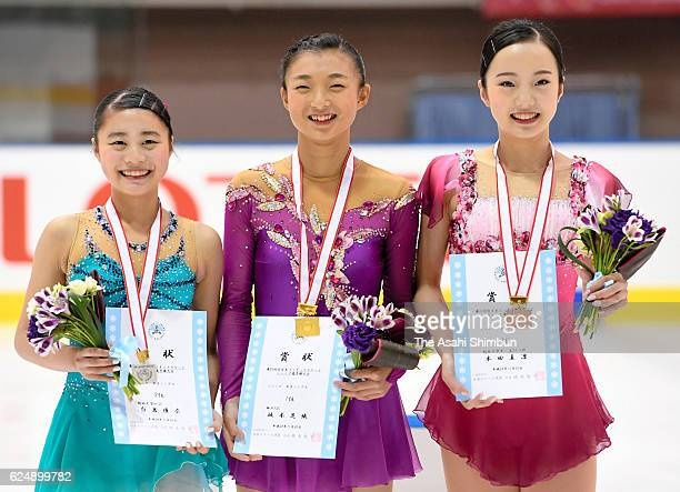 Second place Yuna Shiraiwa winner Kaori Sakamoto and third place Marin Honda pose on the podium at the medal ceremony for the Girls Singles during...