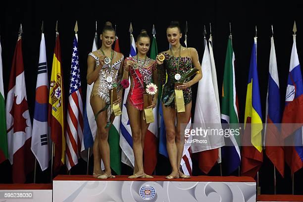 Second placed Aleksandra Soldatova of Russia with Arina Averina of Russia and Winner Ganna Rizatdinova of Ukraine in the podium after the ribbon...