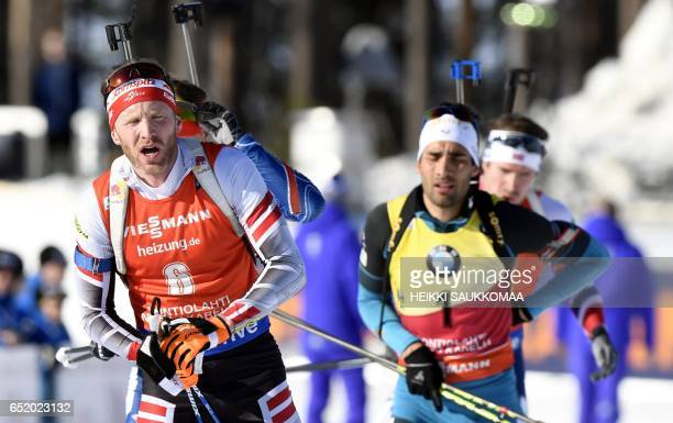Second placed Austria's Simon Eder and fifth placed Martin Fourcade of France compete during the men's 125 km pursuit at the IBU Biathlon World Cup...