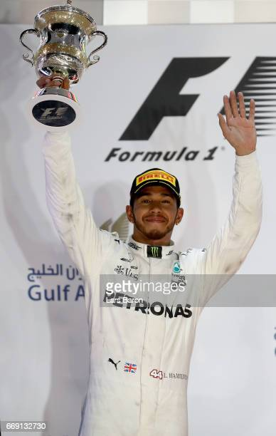 Second placed driver Lewis Hamilton of Great Britain and Mercedes GP celebrates with his trophy on the podium during the Bahrain Formula One Grand...