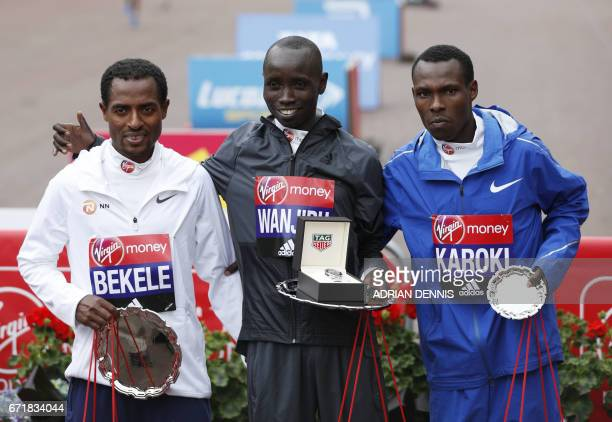 Second placed Ethiopia's Kenenisa Bekele winner Kenya's Daniel Wanjiru and third placed Kenya's Bedan Karoki pose on the podium after the Men's elite...