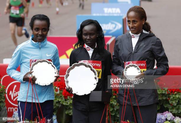 Second placed Ethiopia's Tirunesh Dibaba winner Kenya's Mary Keitany and third placed Ethiopia's Aselefech Mergia pose on the podium after the...
