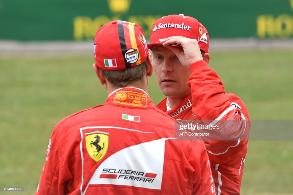 Second placed Ferrari's Finnish driver Kimi Raikkonen (R) speaks with teammate third placed Ferrari's German driver Sebastian Vettel after the qualifying session at the Silverstone motor racing circuit in Silverstone, central England on July 15, 2017 ahead of the British Formula One Grand Prix. / AFP PHOTO / Andrej ISAKOVIC
