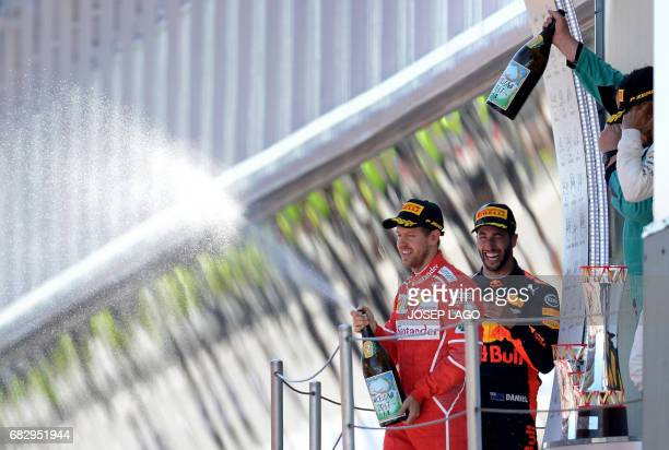 Second placed Ferrari's German driver Sebastian Vettel celebrates on the podium with third placed Red Bull's Australian driver Daniel Ricciardo and...